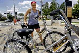 Photo - Lara Vetoyanis prepares to ride a bike in downtown as she pulls a Spokies bike share rental bike out of the rack located next to the Cox Convention Center on Monday, July 1, 2013 in Oklahoma City, Okla.      Photo by Chris Landsberger, The Oklahoman