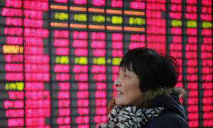 photo - FILE - In this Friday Feb. 8, 2013, file photo, an investor looks at the stock price monitor at a private securities company  in Shanghai, China. U.S. stocks are not alone in racing ahead this year. Many markets in Europe and Asia are trading at multi-year highs, too, in part because of Wall Street's rally. (AP Photo)
