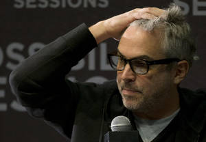 Photo - FILE - In this April 30, 2014 file photo, Oscar-winning Mexican film director Alfonso Cuaron responds to a question during a press conference in Mexico City.  Cuaron published another full-page newspaper ad in Mexican newspapers on Monday, May 5, 2014 asking the president for a series of public debates on reforms to the country's state-owned oil industry. (AP Photo/Rebecca Blackwell, File)