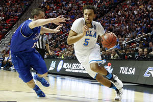 Photo - UCLA forward Kyle Anderson, right, drives with the ball as Tulsa forward Lew Evans defends during the first half of a second-round game in the NCAA men's college basketball tournament Friday, March 21, 2014, in San Diego. (AP Photo/Lenny Ignelzi)