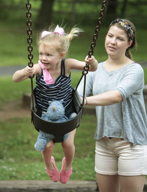 Photo - Olivia Odjeda, 2, gets a push from her babysitter, Annie Turman, while swinging in E.C. Hafer Park in between threats of severe weather and tornados. BY DAVID MCDANIEL, THE OKLAHOMAN. <strong>David McDaniel - The Oklahoman</strong>