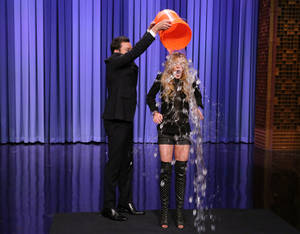 This Aug. 20, 2014 photo released by NBC shows host Jimmy Fallon, left, dumping a bucket of ice water over the head of actress Lindsay Lohan as she participates in the ALS Ice Bucket Challenge on The Tonight Show Starring Jimmy Fallon, in New York. The phenomenal success of the fundraising craze is making charitable organizations rethink how they connect with a younger generation of potential donors, specifically through social media. (AP Photo/NBC, Douglas Gorenstein)