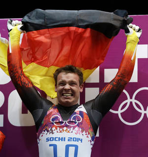Photo - Felix Loch of Germany waves the German flag before the flower ceremony after he won the gold medal during the men's singles luge final at the 2014 Winter Olympics, Sunday, Feb. 9, 2014, in Krasnaya Polyana, Russia.  (AP Photo/Natacha Pisarenko)