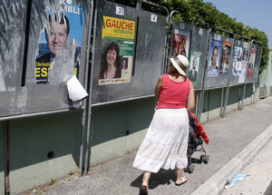 Photo -   A woman looks at posters for the French general election, in Nice, southeastern France, Saturday, June 9, 2012, on the eve of the first round of the French general election. The second round will take place on June 17t to elect the 14th National Assembly of the 5th Republic. (AP Photo/Lionel Cironneau)