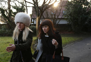 Photo - Italian sisters Francesca, centre, and Elisabetta Grillo, obscured behind her, former personal assistants of English broadcaster Nigella Lawson and her former husband art collector Charles Saatchi, arrive at the Isleworth Crown Court, in west London, Friday, Dec. 20, 2013, during a trial over alleged fraud. Grillos are accused of committing fraud by abusing their positions as PAs by using a company credit card for personal gain between Jan. 1, 2008 and Dec. 31, 2012. (AP Photo/Lefteris Pitarakis)