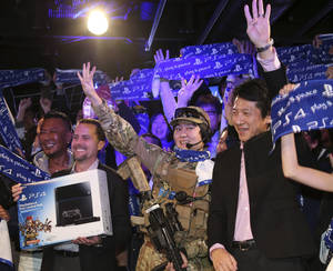 Photo - Sony Computer Entertainment Inc. President and CEO Andrew House, second left, Sony Computer Entertainment Japan President Hiroshi Kawano, right, and first customer of PlayStation 4 , center, pose for photo during launch event in Tokyo, Saturday, Feb. 22, 2014. (AP Photo/Koji Sasahara)