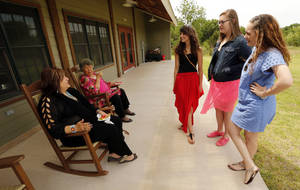 Photo -  Wanda Harfield, left, and Carolyn Claphan sit on the porch of the main building and talk with, from left, Shy-Anna, Meghan and McKenzie Claphan during an open house at Camp ClapHans. The camp is named for Wanda's brother and Carolyn's son and the girl's uncle, Sammy Jack Claphan. PHOTO BY STEVE SISNEY, THE OKLAHOMAN  <strong>STEVE SISNEY -   </strong>