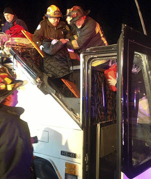 photo - In this photo released by the Boston Fire Department via Twitter, firemen work to remove injured passengers from a bus that hit an bridge as it traveled along Soldiers Field Road in the Allston neighborhood of Boston Saturday night, Feb. 2, 2013. Officials said the bus carryinyg 42 people was traveling from Harvard University home to Pennsylvania when it struck the overpass. (AP Photo/Boston Fire Department)