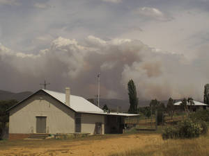 Photo - Wildfire smoke rises from hills behind the village of Numeralla in New South Wales state on Tuesday, Jan. 8, 2013. Wildfires raged across much of southeast Australia. (AP Photo/Rod McGuirk)