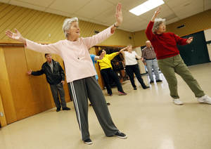 Photo - Jo Manning, 86, left, and Kim Schlegel, 78, right, practice tai chi with other senior citizens at the Will Rogers Park Senior Activity Center, 3501 Pat Murphy Dr., Wednesday, Jan. 22, 2014. Photo by Nate Billings, The Oklahoman