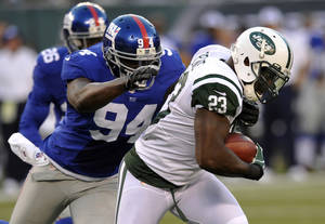 Photo -   New York Jets running back Shonn Greene, right, charges past New York Giants linebacker Mathias Kiwanuka during the first half of a preseason NFL football game between the New York Jets and the New York Giants Saturday, Aug. 18, 2012, in East Rutherford, N.J. (AP Photo/Bill Kostroun)