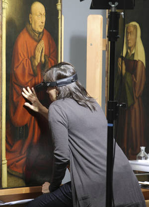 Photo -   FILE - In this Oct. 11, 2012 file photo, a restorer inspects one of the 24 framed panels of the Altarpiece or Adoration of the Mystic Lamb, at the Fine Arts museum in Ghent, Belgium. If Rotterdam's stunning heist of Picasso, Monet and Matisse paintings last month focused attention on the murky world of art theft, Ghent's gothic Saint Bavo cathedral has been at the center of a crime that has bedeviled the art world for decades. The Just Judges panel of the Van Eyck brothers' multi-panel Gothic masterpiece hasn't been seen since 1934, when chief suspect Arsene Goedertier suffered a stroke at a political rally close to Ghent and died after murmuring possibe clues to the crime to a confidant. (AP Photo/Yves Logghe, File)