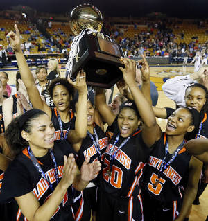 Photo - The Booker T. Washington Hornets celebrate with the gold ball after the Class 6A girls championship high school basketball game in the state tournament at the Mabee Center in Tulsa, Okla., Saturday, March 9, 2013. Booker T. Washington beat Bixby, 52-46. Photo by Nate Billings, The Oklahoman