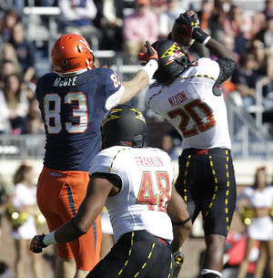 Photo -   Maryland defensive back Anthony Nixon (20) intercepts a pass in front of Virginia tight end Jake McGee (83) as Maryland defensive back Eric Franklin (48) covers during an NCAA college football game at Scott Stadium in Charlottesville, Va., Saturday, Oct. 13, 2012.(AP Photo/Steve Helber)