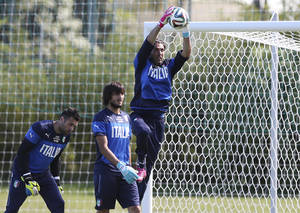 Photo - Italy's Gianluigi Buffon catches the ball as teammates Salvatore Sirigu, left, and Mattia Perin stand by as they train in Mangaratiba, Brazil, Thursday, June 12, 2014. Italy plays in group D at the World Cup. (AP Photo/Antonio Calanni)
