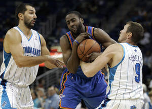 photo - Oklahoma City Thunder guard James Harden, center, fights for the ball with New Orleans Hornets forward Peja Stojakovic, left, of Serbia, and forward Darius Songaila (9), of Lithuania, during the second half of an NBA preseason basketball game at the New Orleans Arena in New Orleans on Saturday. AP Photo