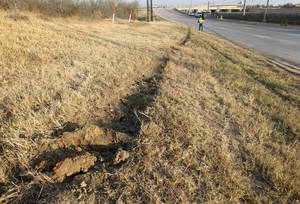 Photo - Tire ruts are seen on the ground with skid marks, at rear on road, at the site of single vehicle accident involving Dallas Cowboys player Josh Brent as a news cameraman, rear, films the area, Saturday, Dec. 8, 2012, in Irving, Texas. Brent is facing an intoxication manslaughter charge after a one-vehicle accident that killed linebacker Jerry Brown, a member of the team's practice squad. (AP Photo/Tony Gutierrez)