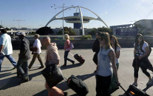 Photo - People exit Los Angeles International Airport in Los Angeles Friday, Nov. 1, 2013. A man pulled a rifle from a bag and shot his way past a security checkpoint at Los Angeles International Airport on Friday, killing one Transportation Security Administration officer and wounding several others, authorities said. (AP Photo/Gregory Bull)