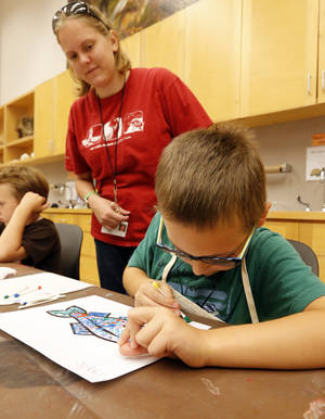 Photo -  Teacher Sarah Novak works with Gabe Van Horn, 7, at the Sam Noble Museum in Norman. Photo by Steve Sisney, The Oklahoman  <strong>STEVE SISNEY</strong>