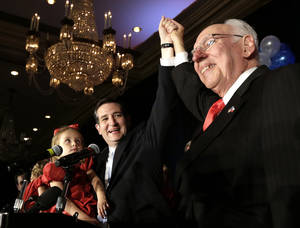 photo -   Republican candidate for U.S. Senate Ted Cruz, left, raises his hand with his father Rafael, right, while holding his daughter Caroline during a victory speech Tuesday, Nov. 6, 2012, in Houston. Cruz defeated Democrat Paul Sadler to replace retiring U.S. Sen. Kay Bailey Hutchison. (AP Photo/David J. Phillip)