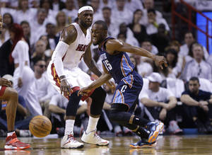 Photo - Charlotte Bobcats' Kemba Walker (15) and Miami Heat's LeBron James (6) eye a loose ball during the first half in Game 1 of an opening-round NBA basketball playoff series, Sunday, April 20, 2014, in Miami. (AP Photo/Lynne Sladky)