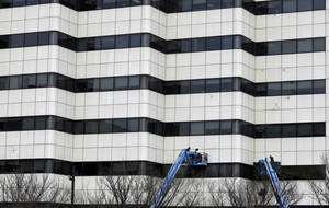Photo - In this Monday, Jan. 20, 2014 photo, workers use bucket lifts as they work on an office building, in Trenton, N.J.  The Commerce Department releases construction spending for December on Monday, Feb. 3, 2014. (AP Photo/Mel Evans)