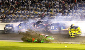 Photo - Danica Patrick, front center, slides through the infield as Tony Stewart, left, Jeff Gordon (24), Kurt Busch (41), Ricky Stenhouse Jr. (17) and Matt Kenseth, right, crash on the front stretch during the NASCAR Sprint Unlimited auto race at Daytona International Speedway in Daytona Beach, Fla., Saturday, Feb. 15, 2014. (AP Photo/Terry Renna)