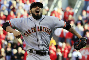 Photo -   San Francisco Giants relief pitcher Sergio Romo celebrates after the Giants defeated the Cincinnati Reds 6-4 in Game 5 of the National League division baseball series, Thursday, Oct. 11, 2012, in Cincinnati. The Giants won the final three games, all in Cincinnati, and advanced to the NL championship series. (AP Photo/Al Behrman)