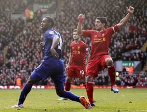 Photo - Liverpool's Luis Suarez, right, scores his team's third goal during their English Premier League soccer match against Cardiff City at Anfield, Liverpool, England, Saturday, Dec. 21, 2013. (AP Photo/Peter Byrne, PA Wire)   UNITED KINGDOM OUT  -  NO SALES  -  NO ARCHIVES
