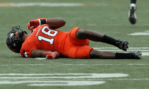 Photo - INJURED: Oklahoma State's Devin Hedgepeth (18) lies on the turf after an injury during a college football game between Oklahoma State University (OSU) and the University of Louisiana-Lafayette (ULL) at Boone Pickens Stadium in Stillwater, Okla., Saturday, Sept. 15, 2012. Photo by Sarah Phipps, The Oklahoman