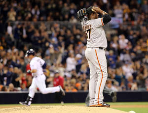 Photo - San Francisco Giants relief pitcher Juan Gutierrez looks to the outfield after giving up a solo home run to San Diego Padres' Yasmadi Grandal in the eighth inning of a MLB baseball game Friday, April 18, 2014, in San Diego. San Diego Padres won 2-1. (AP Photo/Don Boomer)