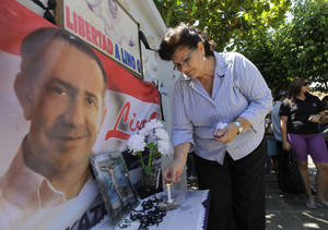 Photo - A supporter of Paraguayan presidential candidate, former Gen. Lino Oviedo, lights a candle at a makeshift memorial, backdropped by one of his campaign posters, at the entrance of the morgue where his remains were taken, in Asuncion, Paraguay, Monday, Feb. 4, 2013. The presidential hopeful died Saturday in a helicopter crash. Oviedo was returning with his bodyguard from a political rally in northern Paraguay Saturday night when his pilot encountered bad weather. All three were killed in the crash. (AP Photo/Jorge Saenz)