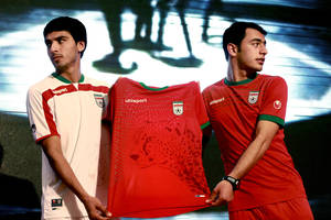 Photo - In this Saturday, Feb. 1, 2014 photo, Iranian soccer players Mohammad Reza Bazaj, right, and Meysam Joudaki present the Iranian national soccer team's newly designed t-shirt for the upcoming Brazil 2014 World Cup, during a conference at a hotel in Tehran. Iran is conducting a campaign to rescue the Asiatic Cheetah which has disappeared across south and central asia except fewer than 100 remaining in Iran. (AP Photo/Vahid Salemi)(AP Photo/Ebrahim Noroozi)