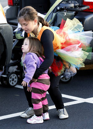 Photo - Brynn McMillan, 9, and sister Elliot McMillan, 18 months, arrive in costume for the Monster Dash.