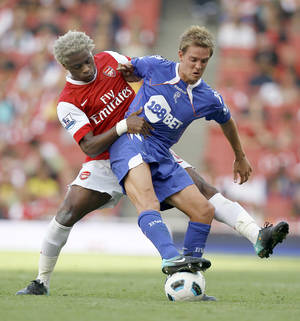 Photo - FILE- In this Sept. 11, 2010, file photo, Arsenal's Alexandre Song, left, vies for the ball with Bolton Wanderers' Stuart Holden during an English Premier League soccer match at Arsenal's Emirates Stadium in London. Holden is set to play his first match since being sidelined by another major knee injury last year.  Bolton manager Dougie Freedman says Holden will play Monday, March 3, 2014 for the English team's under-21s against Everton. (AP Photo/Kirsty Wigglesworth, File)