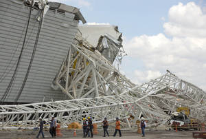 Photo - Civil defense and policemen inspect the damage of an accident at the Arena Corinthians, known locally as the Itaquerao, that will host the 2014 World Cup in Sao Paulo, Brazil, Thursday, Nov. 28, 2013. Two workers were killed when a crane crashed into a 500-ton metal structure that toppled over part of the stadium Wednesday, aggravating already urgent worries that Brazil won't be ready for soccer's showcase event next year. (AP Photo/Andre Penner)