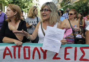 "Photo - Paraskevi Pappa, until this week employed at the Amalia Fleming state hospital, holds up a formal suspension order that places her on reduced pay pending dismissal or obligatory transfer to another state job, as she stands behind a banner which reads in Greek "" layoffs,"" during a protest in Athens, on Thursday, Sept. 12, 2013. Doctors and medical staff from public hospitals gathered outside Greece's Health Ministry to protest mass public sector transfers and lay offs under the government's harsh austerity program. (AP Photo/Petros Giannakouris)"