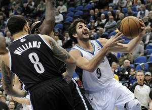 photo - Minnesota Timberwolves' Ricky Rubio, right, of Spain, lays up past Brooklyn Nets' Deron Williams in the first half of an NBA basketball game on Wednesday, Jan. 23, 2013, in Minneapolis. (AP Photo/Jim Mone)