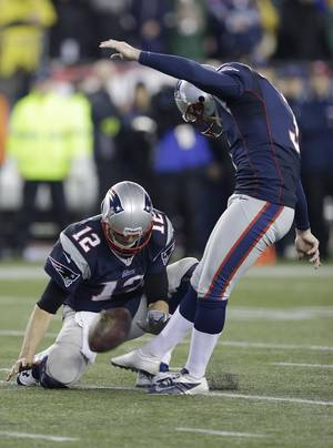 Photo - New England Patriots quarterback Tom Brady (12) holds the ball for an extra point by punter Stephen Gostkowski during the second half of an AFC divisional NFL playoff football game against the Indianapolis Colts in Foxborough, Mass., Saturday, Jan. 11, 2014. (AP Photo/Stephan Savoia)