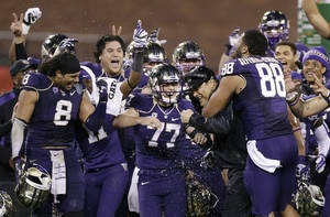 Photo - Washington head coach Marques Tuiasosopo, at right, celebrates with his team after a 31-16 win over BYU during the Fight Hunger Bowl NCAA college football game on Friday, Dec. 27, 2013, in San Francisco. (AP Photo/Marcio Jose Sanchez)