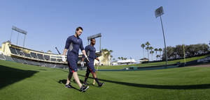 Photo - Atlanta Braves' Chris Johnson, left, and Justin Upton, right, make their way to the batting cages at the Braves' spring training facility Monday, Feb. 11, 2013 in Kissimmee, Fla. The Braves pitchers and catchers first spring training workout is Tuesday. (AP Photo/David J. Phillip)