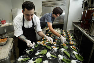"Photo - Kyle Mills and Melissa Scaramucci prepare plates of Asian appetizers for guests at a special food and wine pairing event Thursday at the Sam Noble Oklahoma Museum of Natural History. The after-hours sampling party was held in conjunction with the museum's current ""Chinasaurs"" exhibit. PHOTO BY STEVE SISNEY, THE OKLAHOMAN"