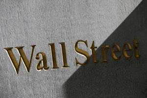 Photo - FILE - This March 4, 2013 file photo shows a sign for Wall Street on the side of building near the New York Stock Exchange, in New York. European stocks advanced Wednesday July 16, 2014 after China's economic growth picked up slightly in the second quarter but Asian markets were lukewarm about the data that largely fitted expectations. (AP Photo/Mark Lennihan, File)