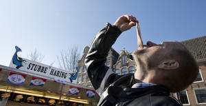 Photo - This March 12, 2014 photo shows Associated Press reporter Mike Corder demonstrating how to eat raw herring outside one of Amsterdam's ubiquitous  herring stands, in the Netherlands. (AP Photo/Peter Dejong)