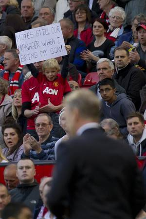Photo - A young supporter holds up a sign as Manchester United's manager David Moyes, below, makes his way down the touchline during his team's 1-1 draw against Southampton in their English Premier League soccer match at Old Trafford Stadium, Manchester, England, Saturday Oct. 19, 2013. (AP Photo/Jon Super)