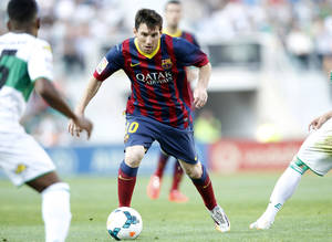 Photo - Barcelona's Lionel Messi from Argentina,  controls the ball past Elche's  Alberto Rivera Pizarro, left, during a Spanish La Liga soccer match at the Martinez Valero stadium in Elche, Spain, on Sunday, May 11, 2014. (AP Photo/Alberto Saiz)