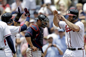 Photo - Atlanta Braves' Evan Gattis, right, high-fives teammate Ramiro Pena after hitting a grand slam in the fourth inning of a baseball game as Minnesota Twins catcher Ryan Doumit, center rear, stands at home plate, Wednesday, May 22, 2013, in Atlanta. (AP Photo/David Goldman)