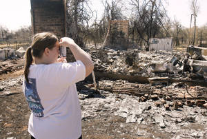 Photo - Tina Cooper takes a picture of the charred remains of her home at 14328 NE 4th St. in Choctaw, Okla.,  Saturday, April 11, 2009. Photo by Paul Hellstern, The Oklahoman