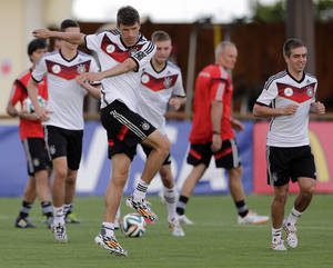 Photo - Germany's national soccer player Thomas Mueller, foreground left, warms up besides teammate Philipp Lahm during a training session in Santo Andre near Porto Seguro, Brazil, Tuesday, June 10, 2014. Germany will play in group G of the 2014 soccer World Cup. (AP Photo/Matthias Schrader)