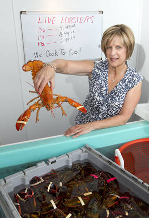 Photo - Paula Coppersmith holds a lobster at Dock's Seafood restaurant and market Thursday in South Portland, where they're selling five lobsters for $24. AP Photo